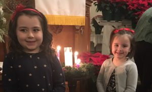 Two young girls standing in front of the Advent Wreath