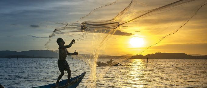 Fisherman casting a net into the see; photo by pixabay