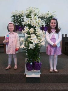 two little girls standing by cross covered in lillies