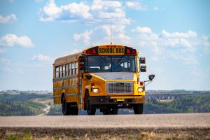 School Bus driving on the road by Denisse Leon, Unsplash