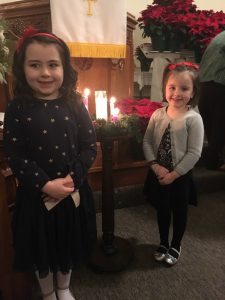 Two girls in front of advent candles