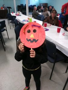 kid with pumpkin craft
