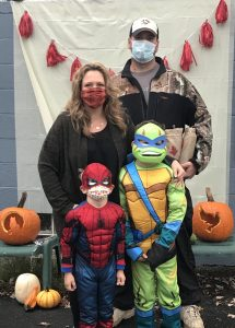 Family of four with kids dressed as spiderman and ninja turtle