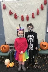 two kids dressed as skelton and unicorn