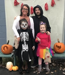 Family of four with kids dressed as skelton and unicorn