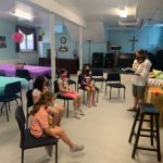 Pastor reading Bible to kids at VBS