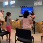 VBS kids singing with volunteer playing guitar